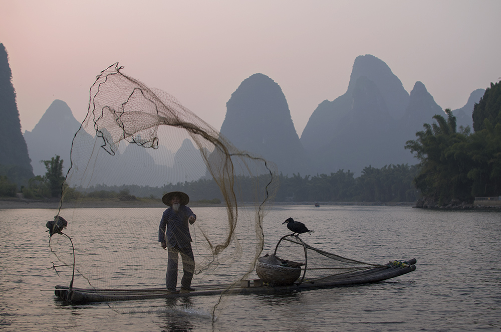 Packing list for China in winter, china winter packing list, cormorant fisherman throwing net at sunset, what to wear in china in winter